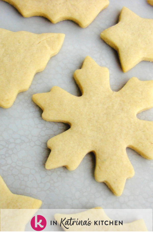 snowflake cut out cookie on table top with other cookies laying beside