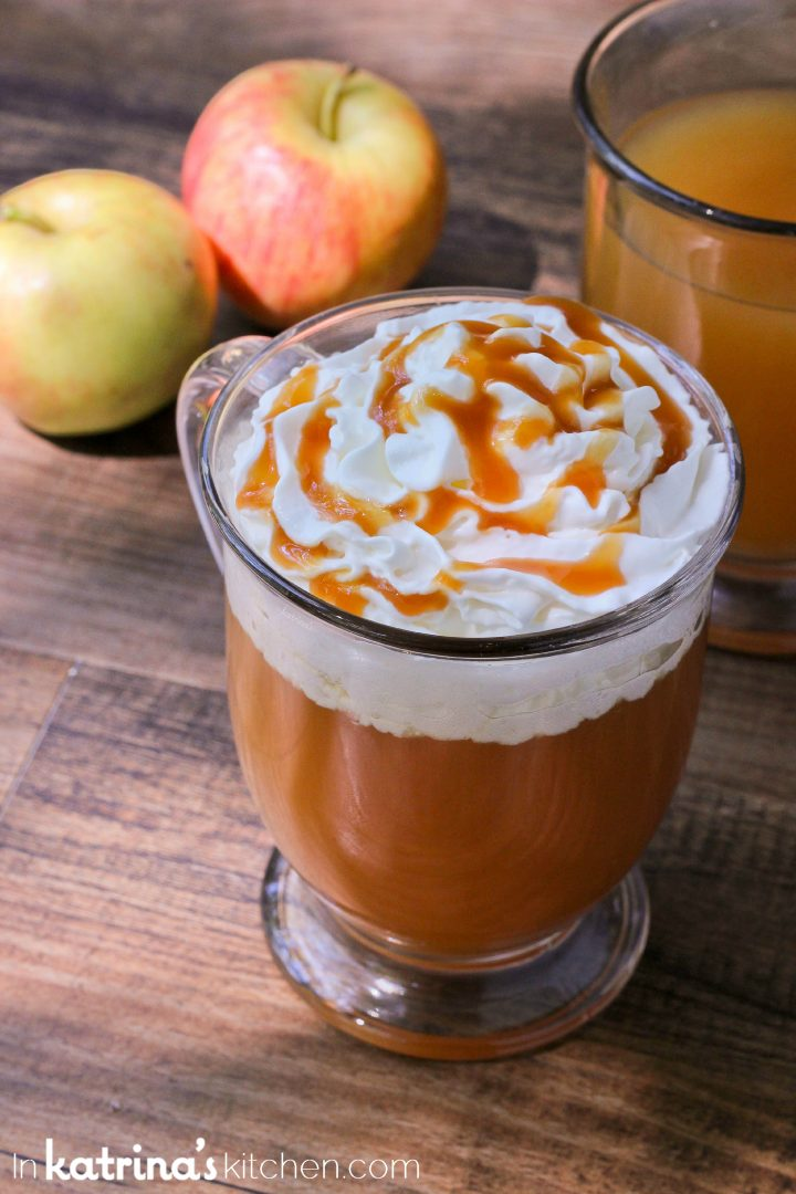 hot apple drink in a clear mug with whipped cream and caramel sauce
