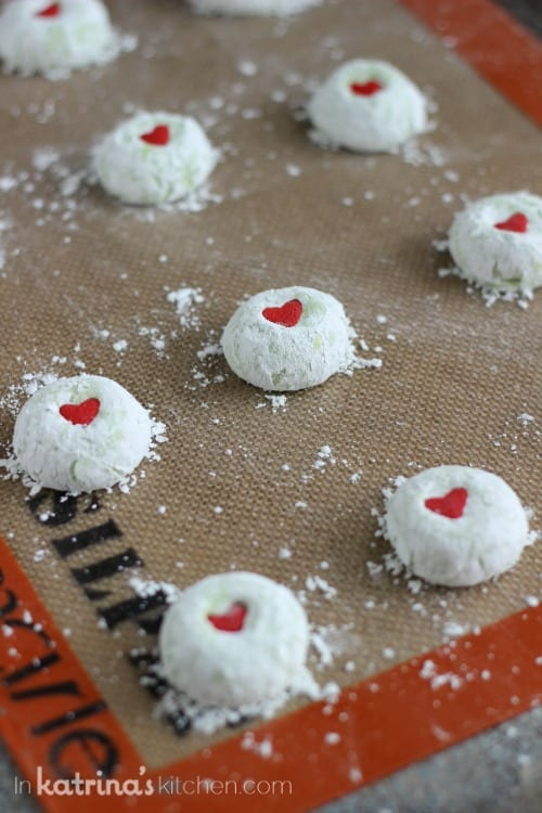 green cookies shown covered in powdered sugar and a red heart lined up on a baking sheet