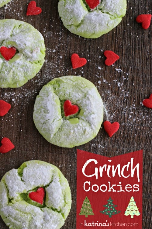 Cake Mix Grinch Cookies shown on a wooden table surrounded by candy heart sprinkles
