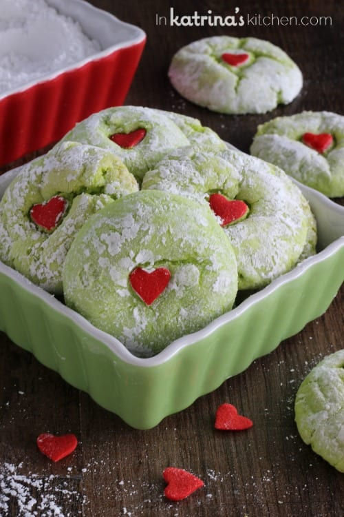 4 green grinch cookies shown in a dish alongside more cookies and sprinkles on a wooden tabletop
