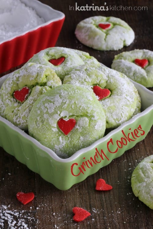 green cookies with a red heart shown in a green dish and the text Grinch Cookies
