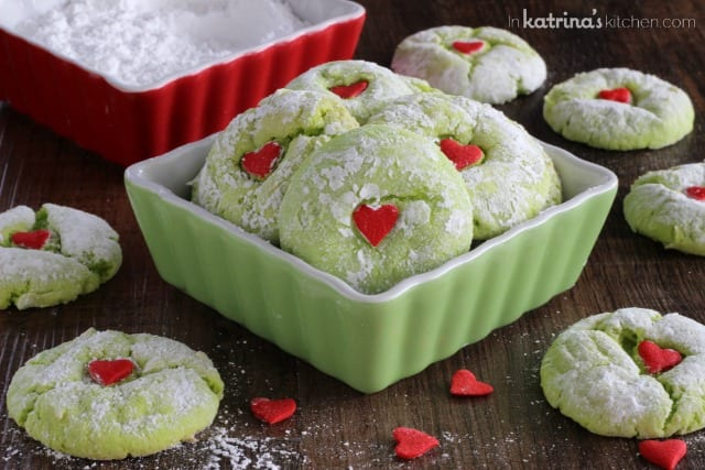 green cookies with red hearts piled into red and green dishes and surrounded by more cookies and heart sprinkles