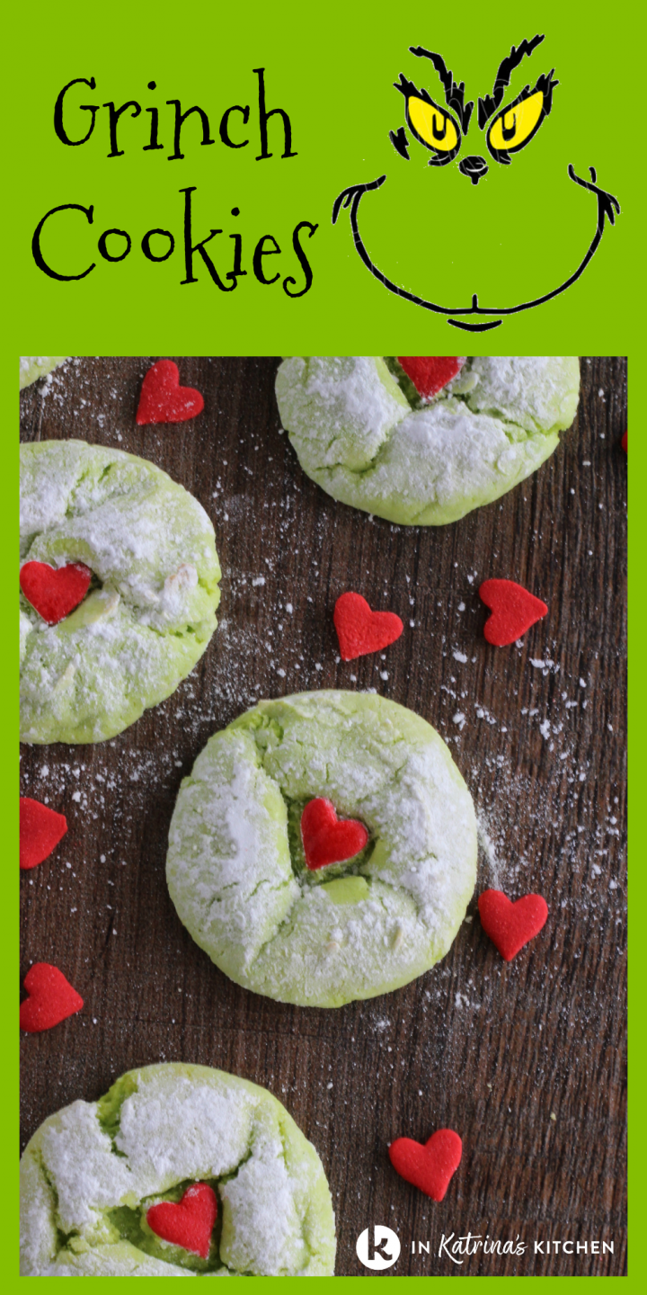 green cookies sprinkled with powdered sugar and a red heart in the center shown with a grinch face