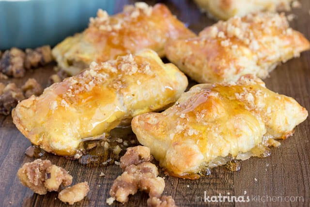 puff pastries on a cutting board drizzled with candied walnuts and honey