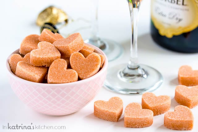 heart-shaped sugar cubes in a pink bowl shown with a bottle of champagne