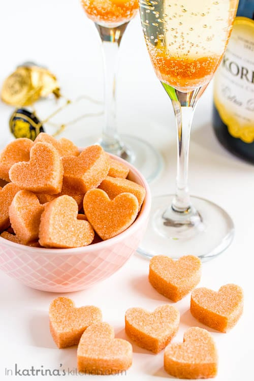 heart-shaped Sugar Cubes shown in and around a pink bowl and champagne flutes