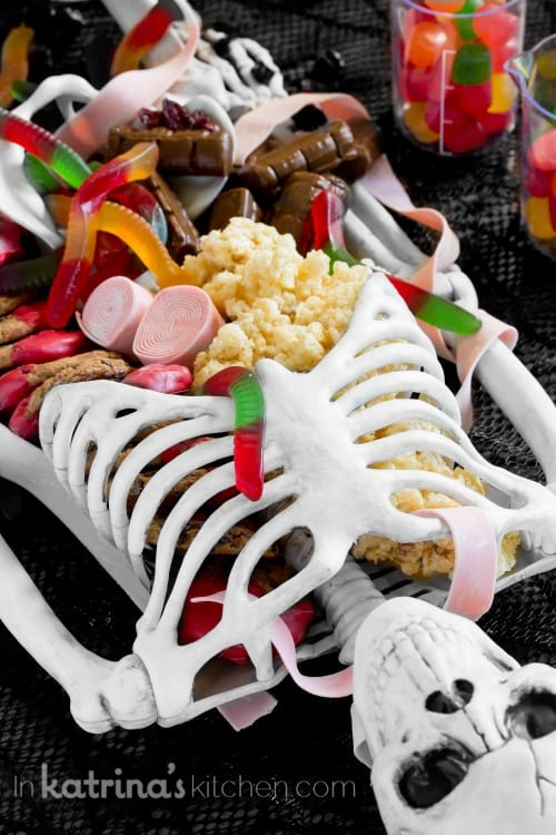candy spilling out of a skeleton on a halloween dessert table