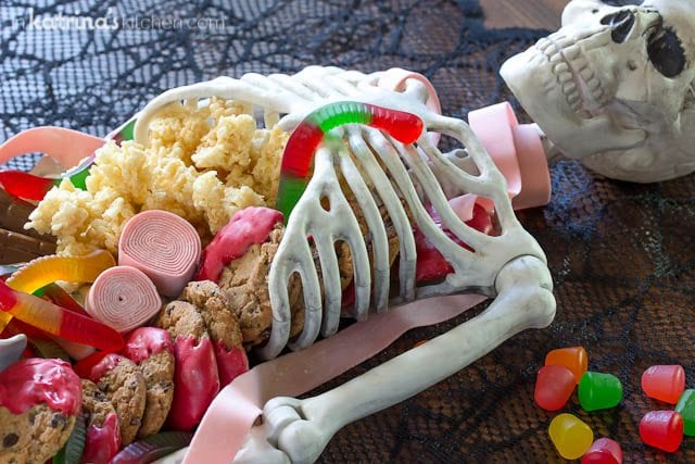 skeleton shown on a tabletop with candy and cookies spilling out of it