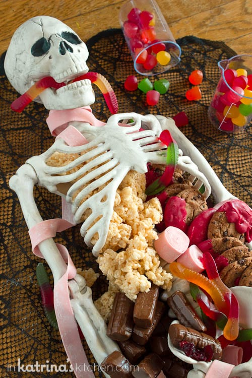 skeleton shown with candy and cookies spilling out of it and a gummy worm crawling out of the skeleton mouth