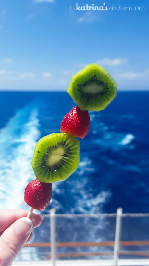 skewered strawberries and kiwi fruit shown with the wake of a cruise ship in the background