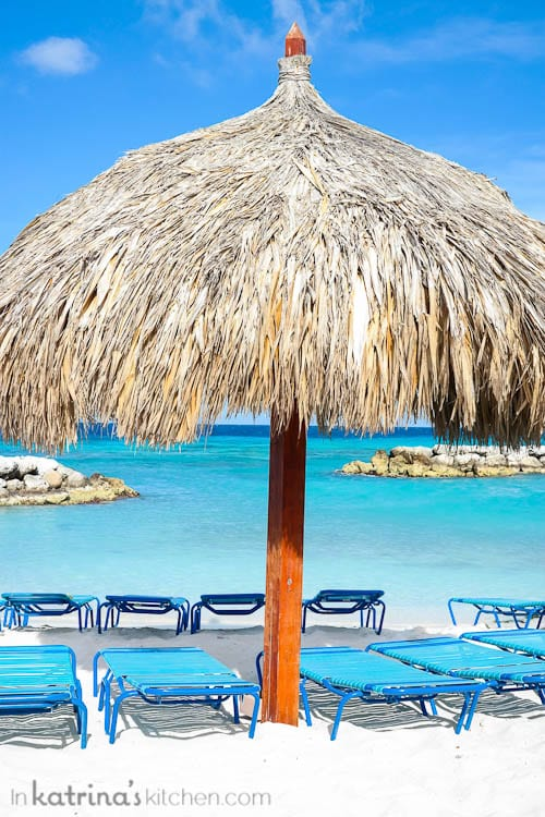 Thatch umbrella with beach chairs in front of the ocean in Aruba