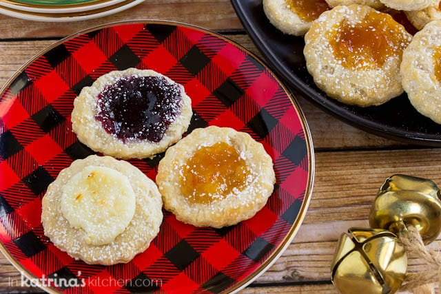 three cookies with jam centers on a red and black checkered plate