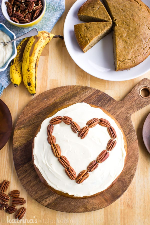 frosted banana bread cake on a serving platter with pecans in a heart shape and slices on smaller plates