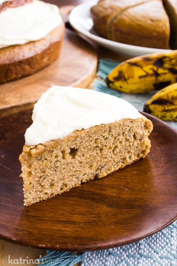 frosted banana bread snack cake with ripe bananas in the background