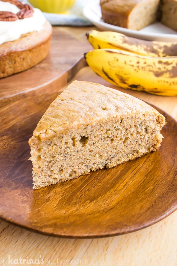 unfrosted slice of banana breadcake on a wooden plate with bananas in the background