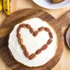frosted banana bread cake on a serving platter with pecans in a heart shape