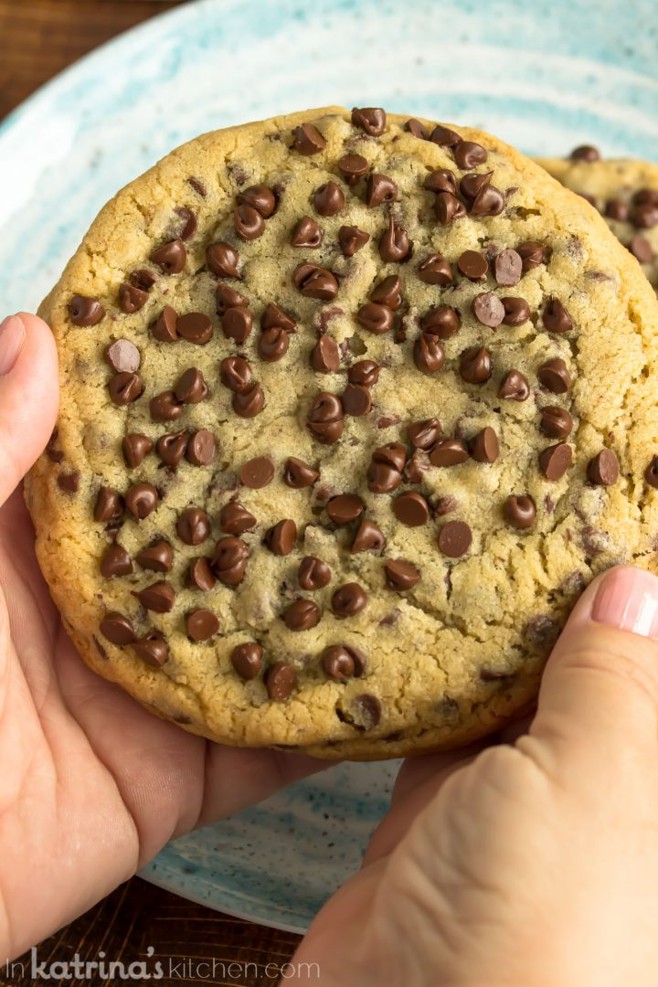 large cookie being held by 2 hands like it is about to be split down the middle
