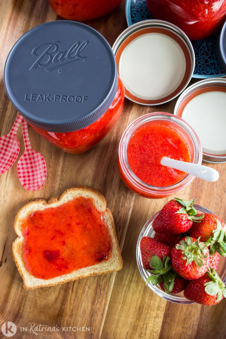 jars of strawberry jam, a glass bowl of strawberries, and jam spread on toast