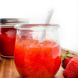 a glass jar of jam beside fresh strawberries