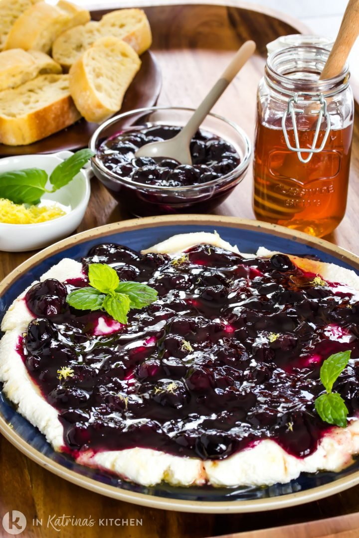goat cheese spread on a plate with blueberry sauce and mint leaves on a wooden tray