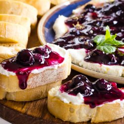 baguette slices covered in whipped goat cheese and dripping blueberry sauce
