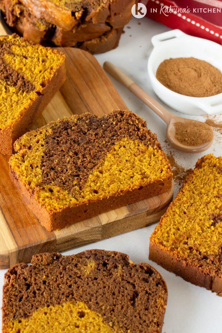 slices of chocolate swirled pumpkin bread on a wooden cutting board with a dish of cinnamon beside