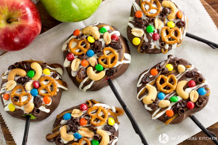 5 caramel apple slices with trail mix toppings on a wooden cutting board with parchment paper underneath