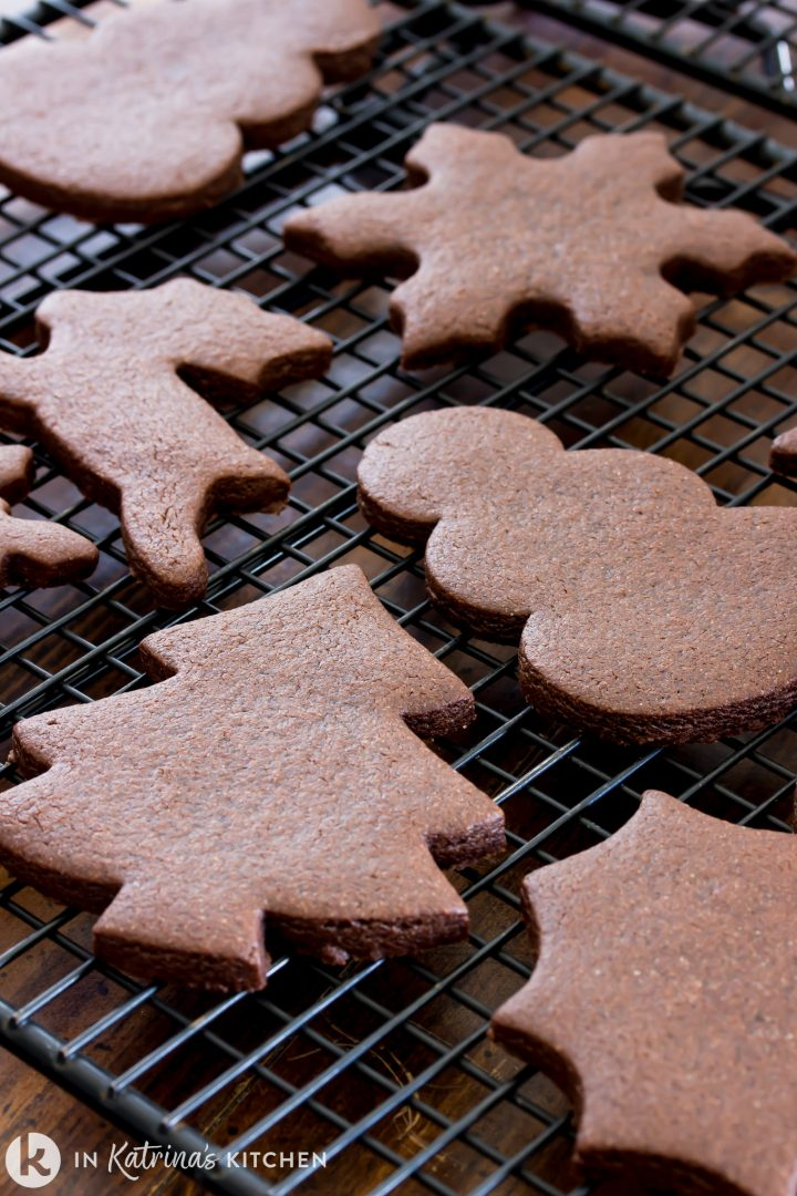 Traditional Christmas cookie shapes in a chocolate cookie shown on a cooling rack
