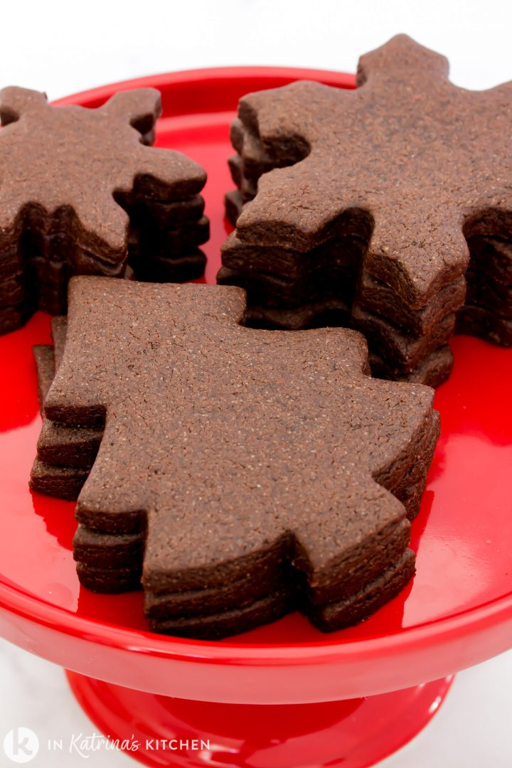 three stacks of chocolate cut out cookies on a red platter- trees, snowflakes, and mini snowflakes