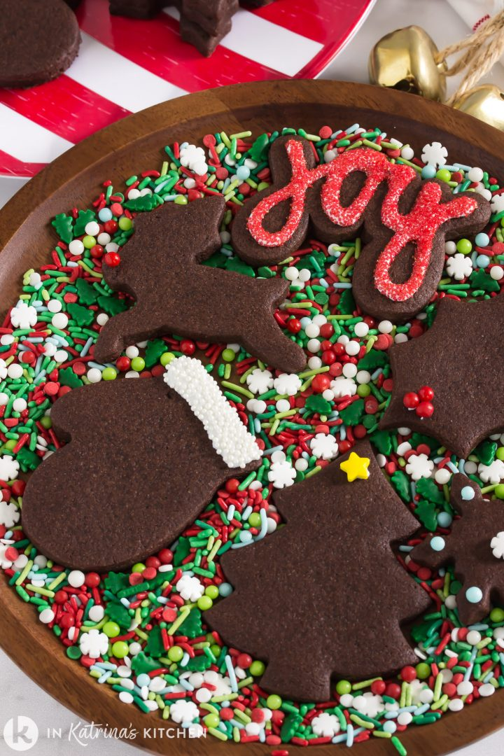 chocolate cut out cookies in Christmas shapes on a wooden try with red and green sprinkles