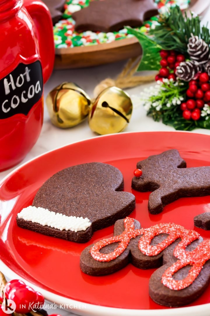 chocolate cut out cookies shown on a red platter with a mug of hot chocolate and golden jingle bells