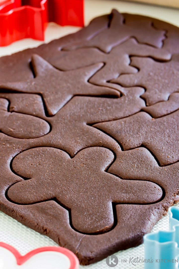 chocolate cut out cookie dough rolled out and cut with traditional cookie cutter shapes like gingerbread man, tree, star, and snowflake