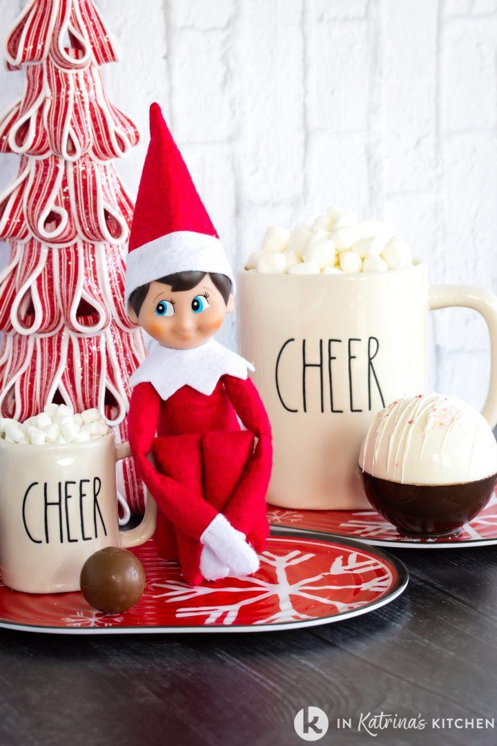 elf with mini mug and chocolate truffle beside regular sized mug and chocolate