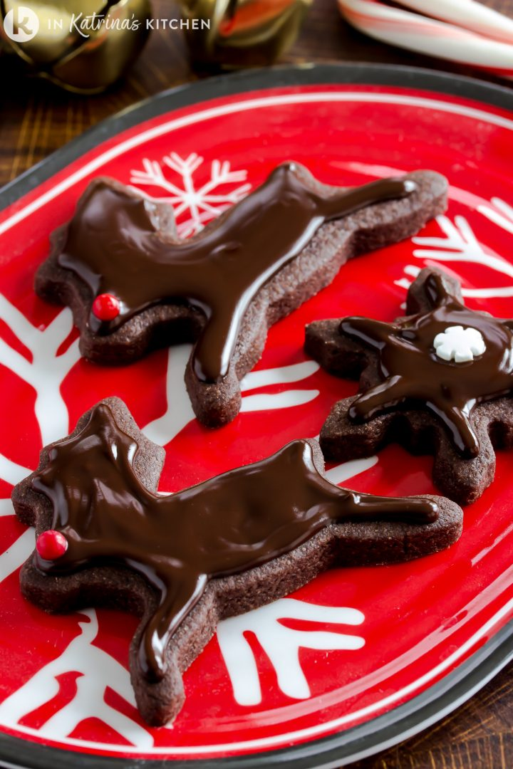 chocolate reindeer cut out cookies with chocolate glaze on a red platter