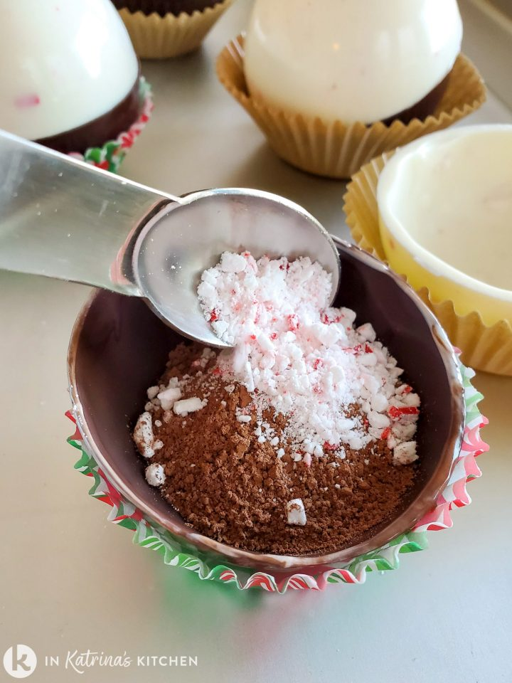 chocolate orb being filled with cocoa powder and crushed candy canes