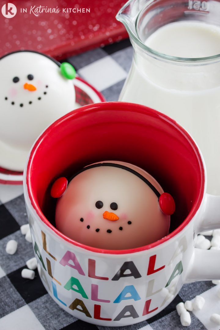 white chocolate snowman in the bottom of a Christmas mug with a glass of milk beside