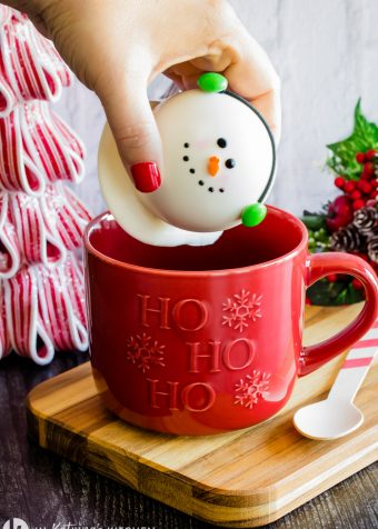 white chocolate snowman with candy ear muffsbeing placed inside a red mug