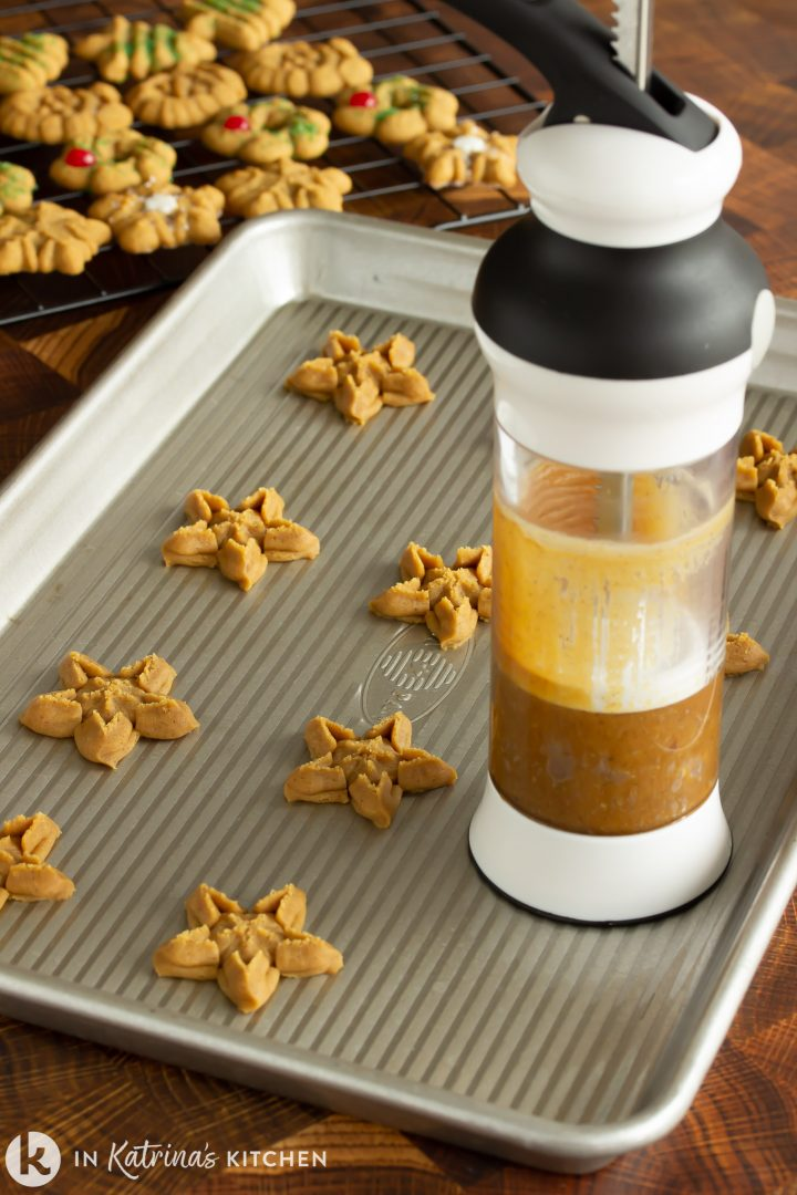 star shaped cookies on a cookie sheet with a spritz cookie gun