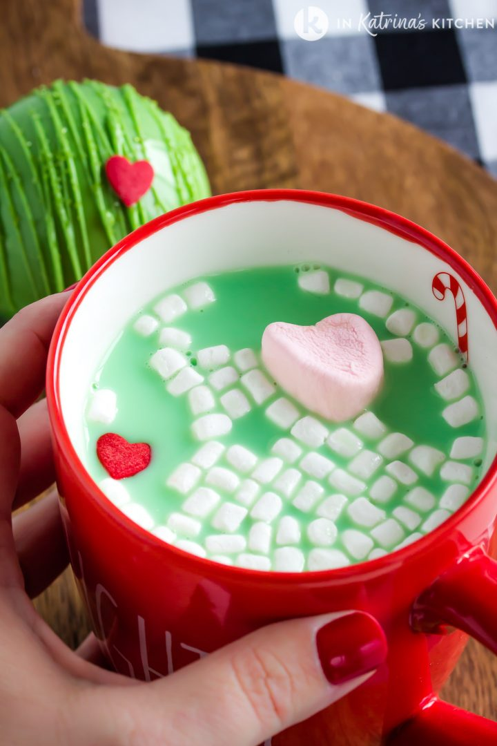 red mug of green hot chocolate with marshmallows and heart candy