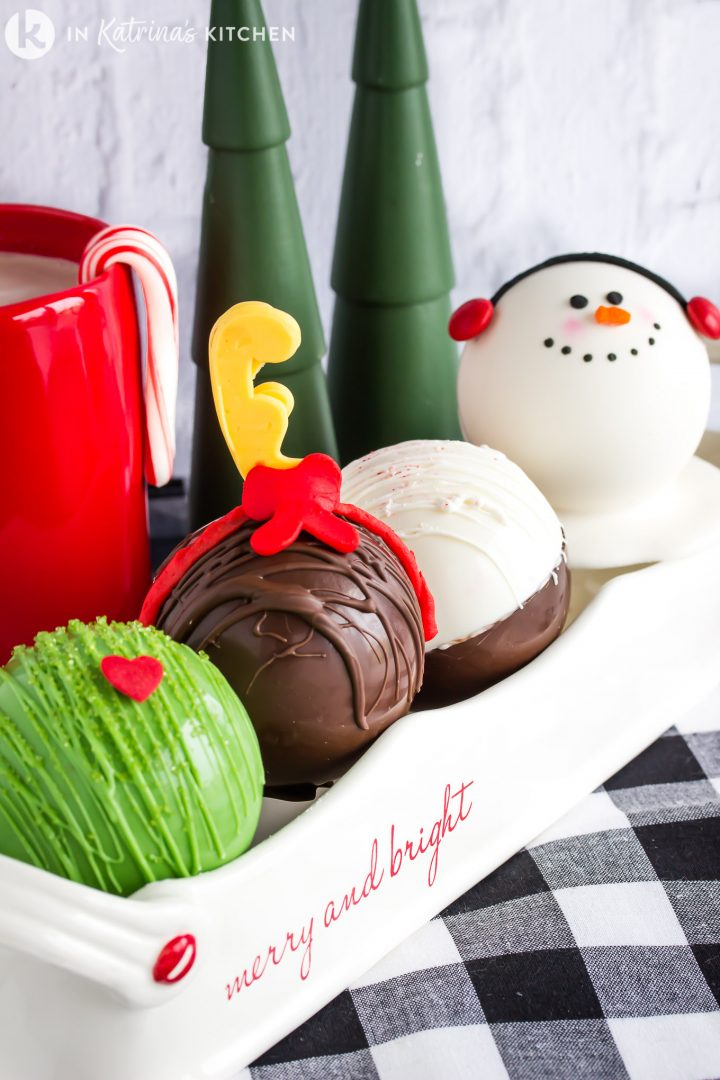 four festive christmas themed hot chocolate bombs lined up in a dish