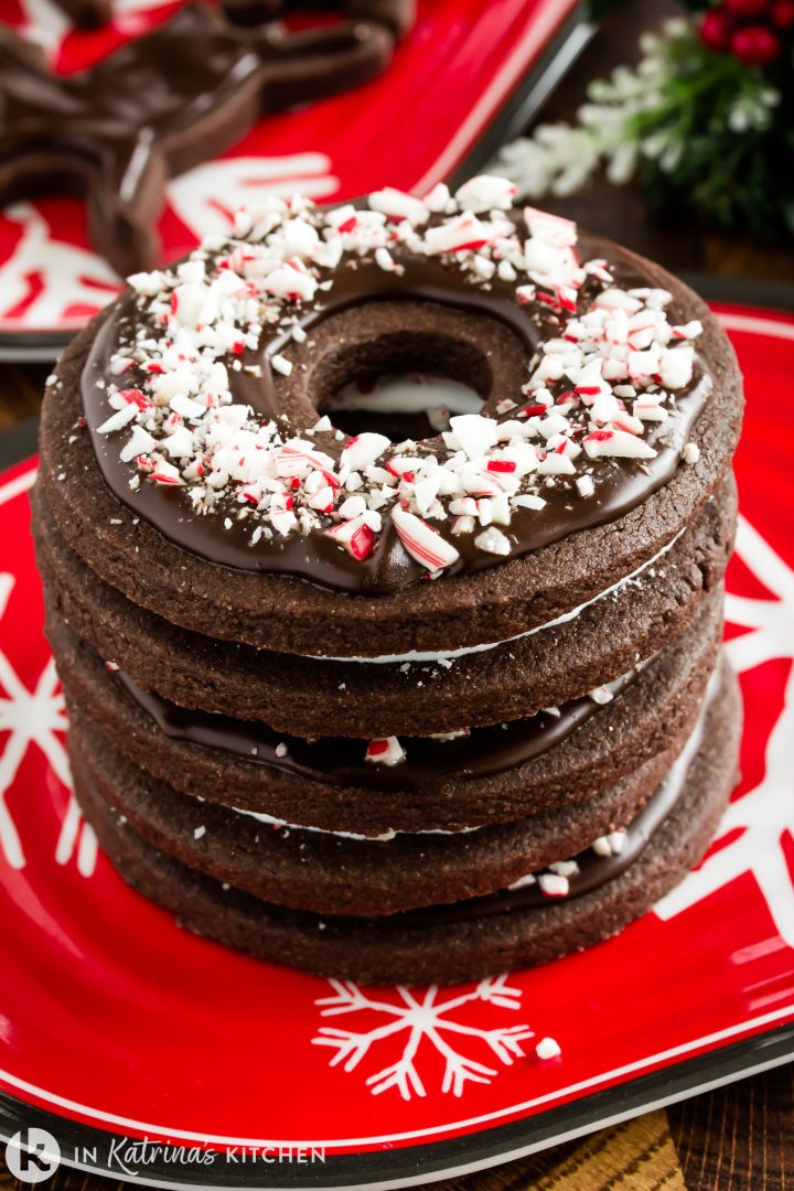 stack of chocolate cookies with crushed candy canes on a red plate