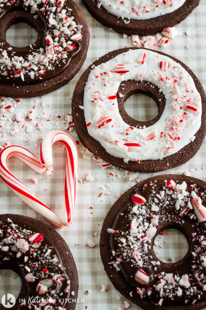 chocolate cookies in the shape of doughnuts shown with glaze and crushed peppermint