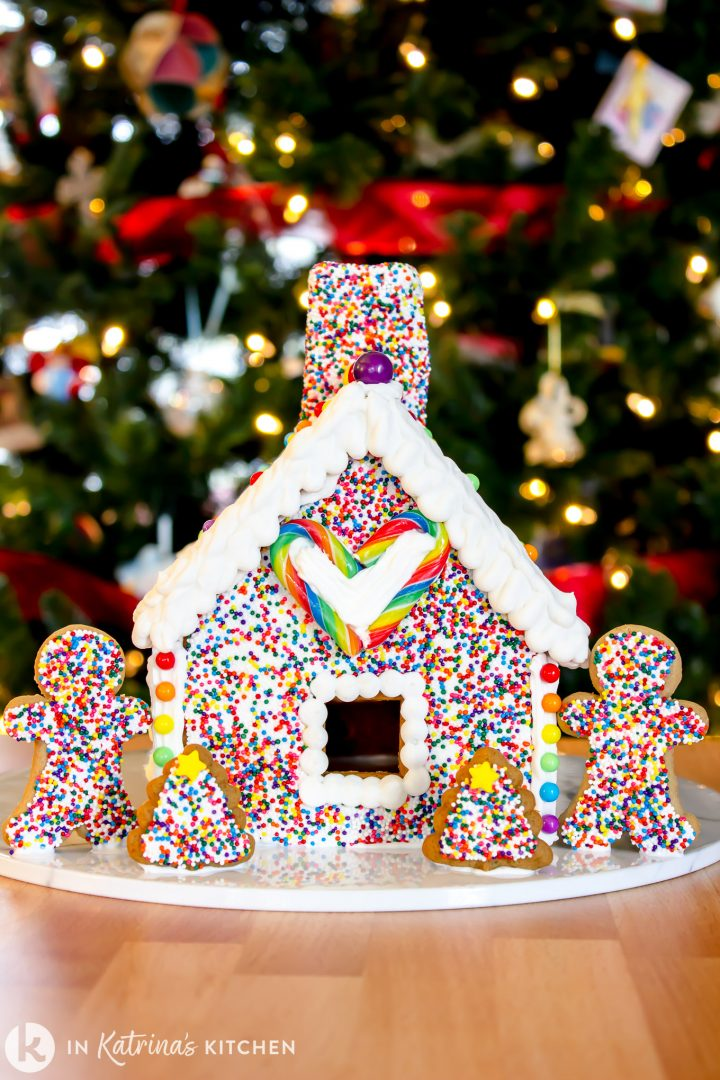 gingerbread house and gingerbread men covered in rainbow sprinkles in front of a sparkling Christmas tree