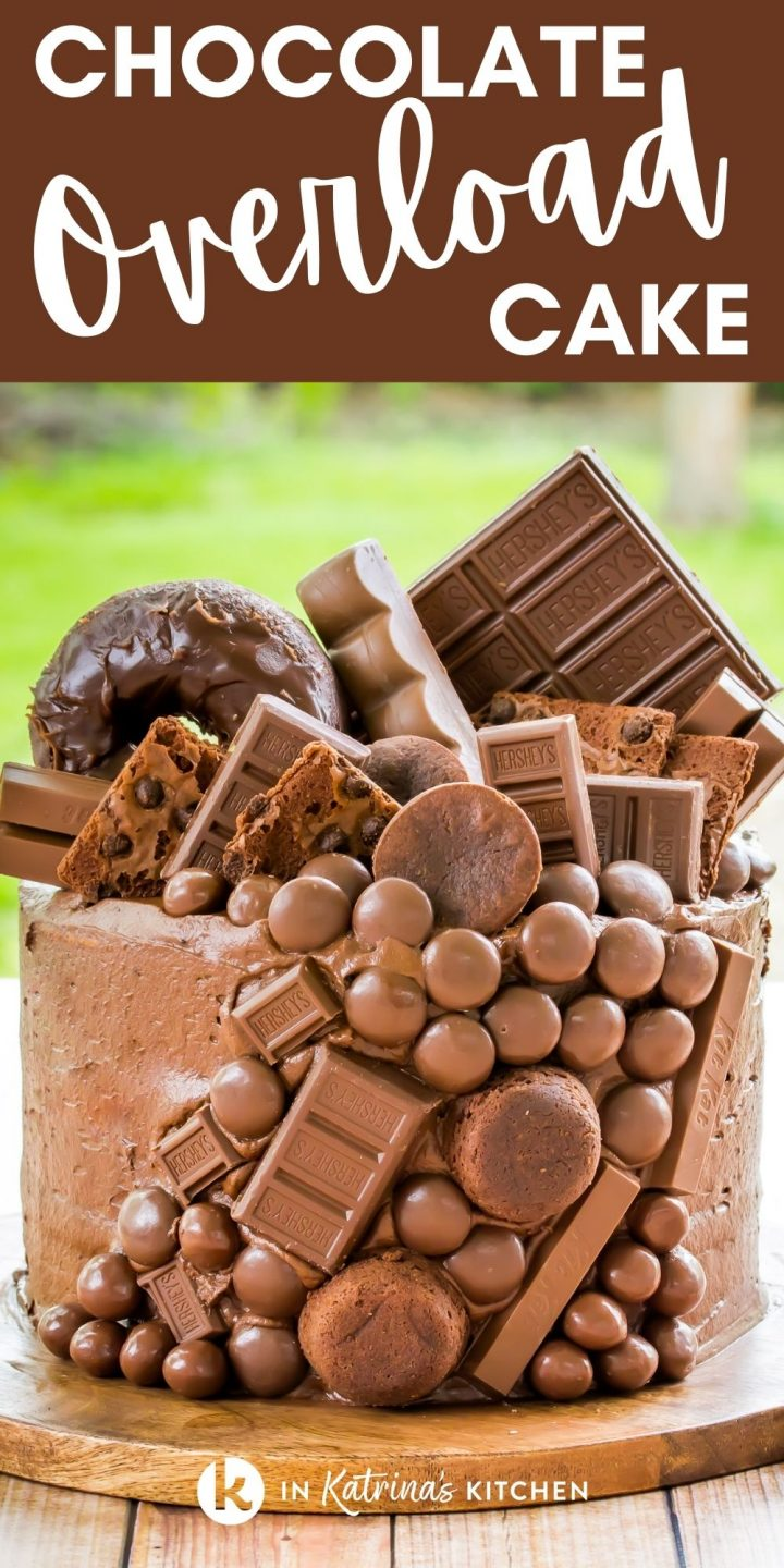 """chocolate cake piled high with chocolate candies, brownies, and doughnuts and the text """"Chocolate Overload Cake"""""""
