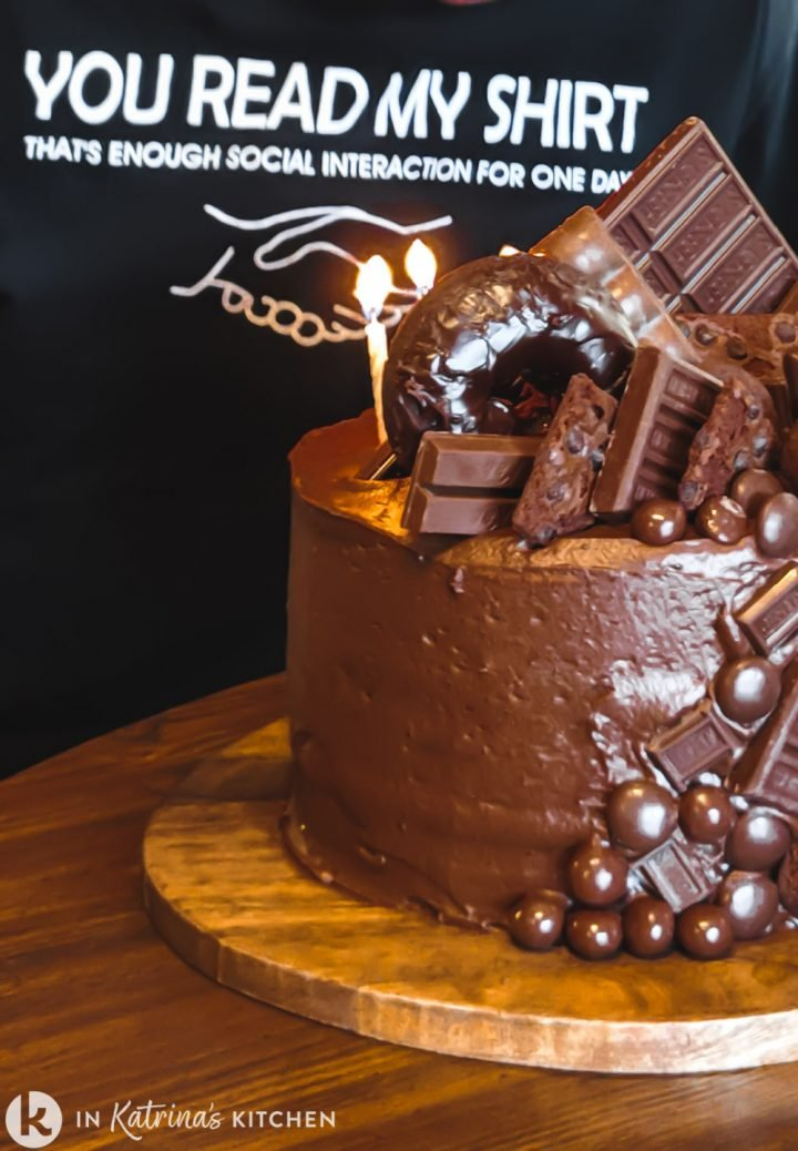chocolate birthday cake with candles being blown out