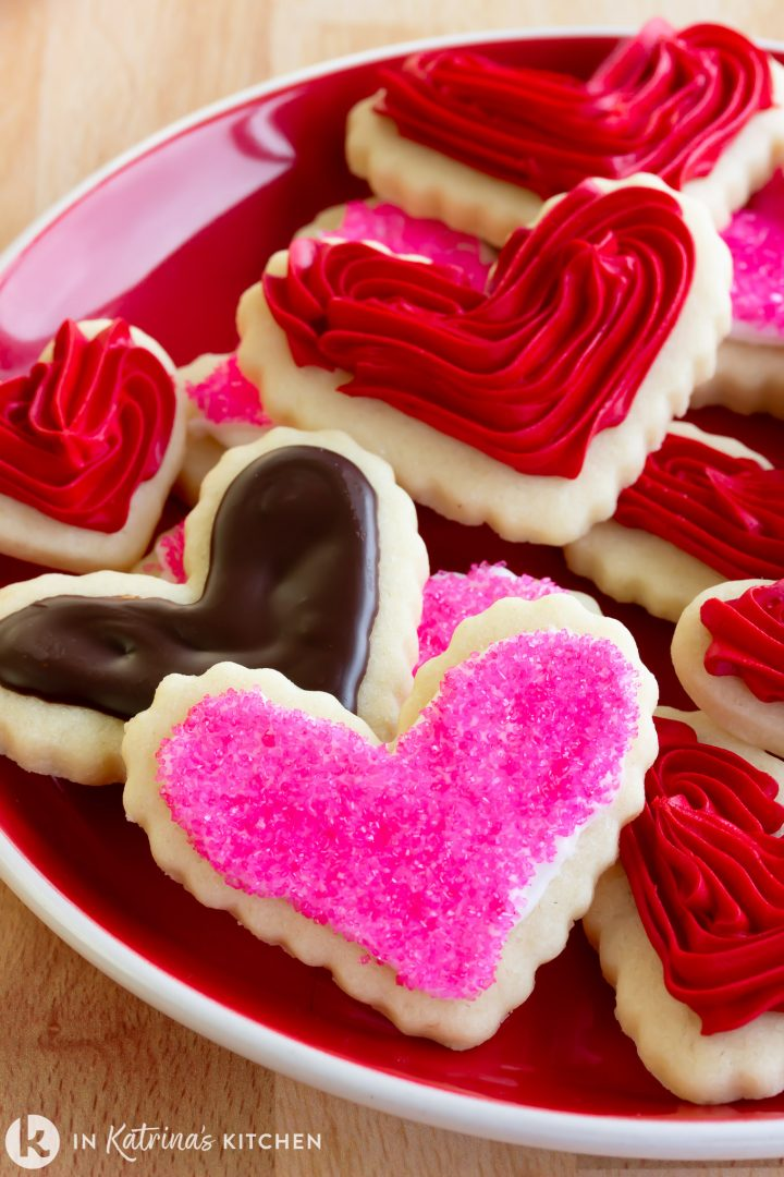 heart-shaped frosted cookies on a red plate