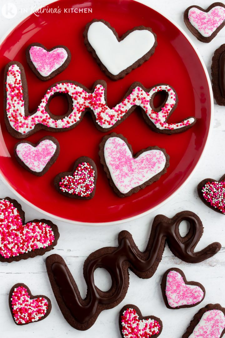 chocolate heart shaped frosted cookies on a red plate with other cookies spelling out the word LOVE