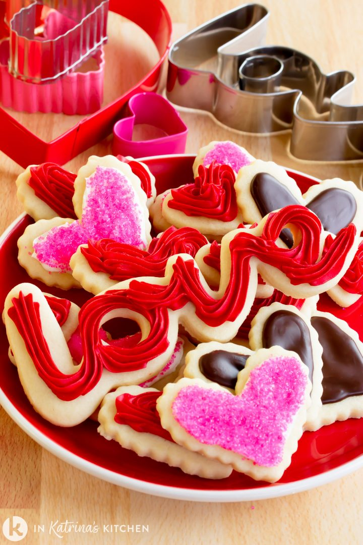 valentine themed cut out frosted sugar cookies on a plate with cookies cutters surrounding