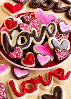 piles of chocolate and vanilla frosted sugar cookies in heart shapes and spelling out the word LOVE